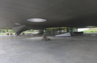 La conception sur pilotis du Musée de la Grande Guerre du pays de Meaux a permis de dégager un vaste rez-de-chaussée servant d'abri avant d'entrer, offrant au visiteur une mise en scène puissante d'objets, d'images et de sons. L'ombre permanente n'est plus vécue comme un abri, mais plutôt comme une mise en condition aux réalités des champs de bataille ; un plafond bas de béton gris comme un ciel toujours menaçant.